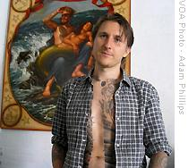 Scott Campbell stands in front of a poster of a man carrying a mermaid